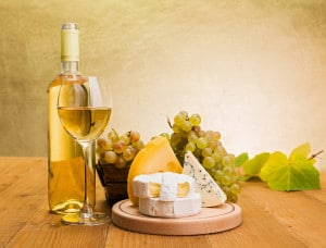 White wine in bottle and glass with grapes, camembert, emmentaler and blue cheese snack, grape leaves decoration